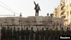 Protestçi prezident köşgini goraýan esgerleriň öňünde täze gurlan haýatyň üstünde hökümete garşy şygara gygyrýar. Kair, 9-njy dekabr, 2012 ý.