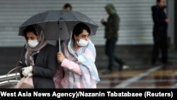 Iranian women wear protective masks to prevent contracting coronavirus, as they walk in the street in Tehran, Iran February 25, 2020.