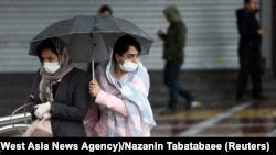 Iranian women wear protective masks to prevent contracting coronavirus, as they walk in the street in Tehran. Iran February 25, 2020.