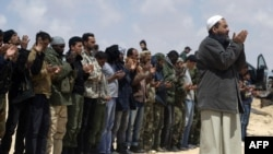 Libyan rebels pray at an area where they are engaged in street battles with forces loyal to Qaddafi near Brega on April 3.