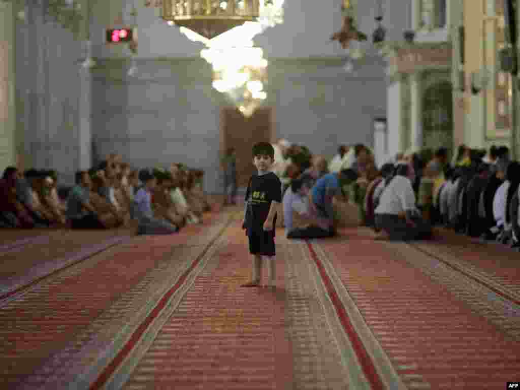 A Muslim boy attends the weekly Friday Prayer at the Omayyad Mosque in central Damascus, Syria, on August 26. Photo by Joseph Eid for AFP