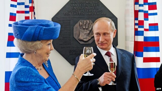 Dutch Queen Beatrix and Russian President Vladimir Putin raise their glasses after they unveiled a plaque during their visit to the Hermitage Museum in Amsterdam on April 8.