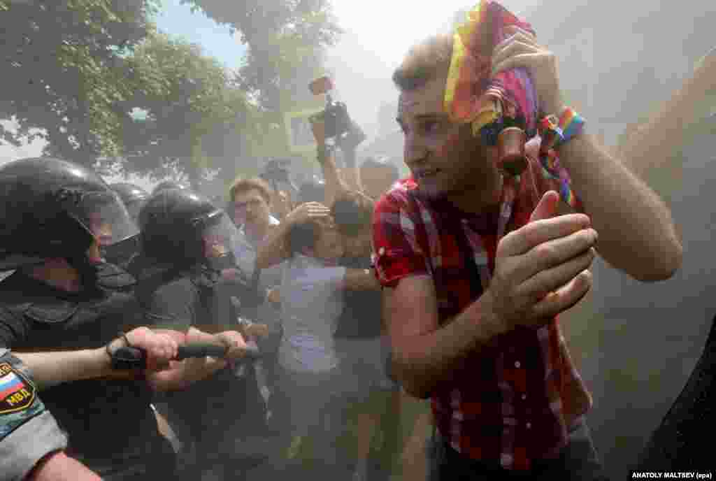 Rights activists run a gauntlet of riot police as debris rains down during a gay pride event in St. Petersburg in 2013.