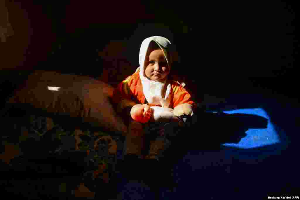 An internally displaced Afghan girl looks on as she holds a doll inside her temporary home at a refugee camp on the outskirts of Herat. (AFP/Hoshang Hashimi)