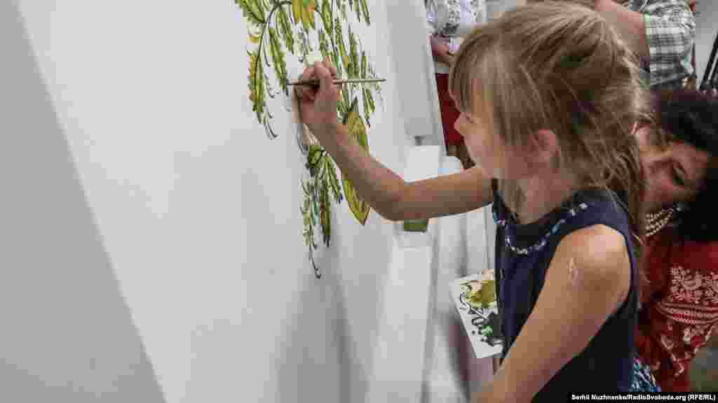 Дівчинка домальовує «дерево життя» майстрині петриківського розпису Галини Назаренко в галереї на території Національного заповідника «Софія Київська»