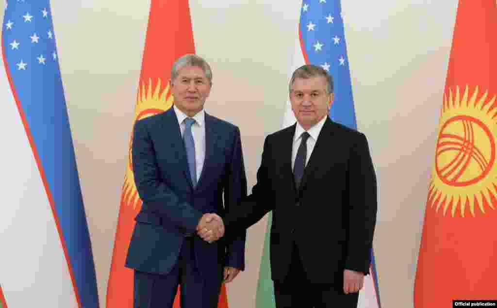 Қырғызстан президенті Алмазбек Атамбаев пен Өзбекстан президенті Шавкат Мирзияев қол алысып тұр.