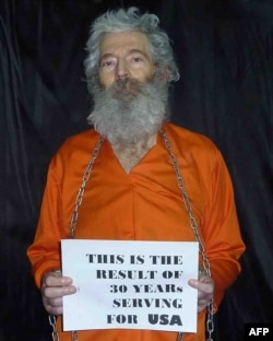 """Роберт Левинсон с плакатом """"Вот результат 30-летней работы на США"""""""