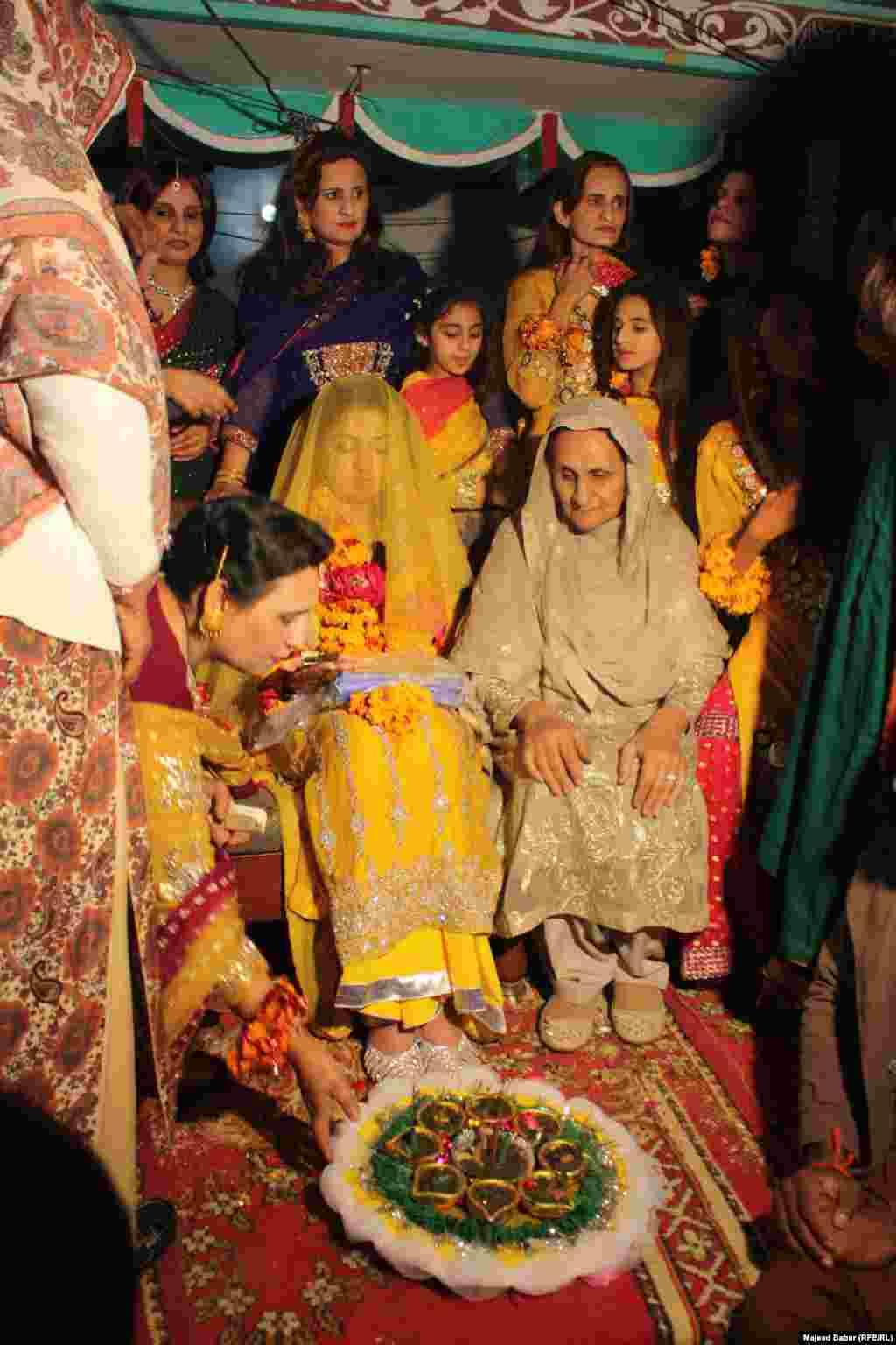 Elderly women apply henna to the bride's feet.