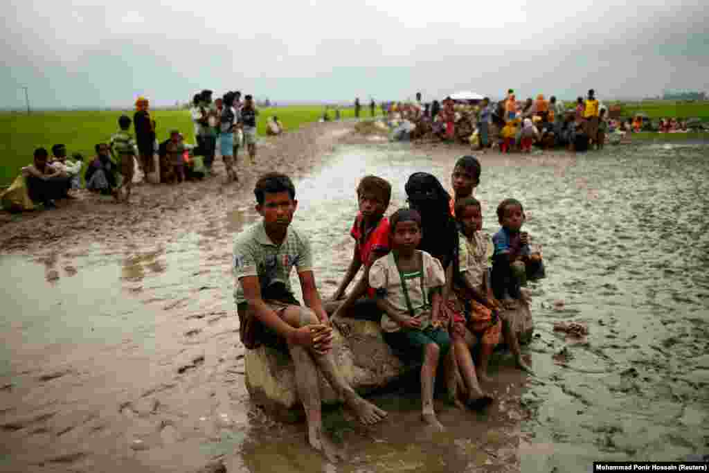 Rohingya refugees sit as they are temporarily held by the Border Guard Bangladesh in an open area after crossing the border in Teknaf. (Reuters/Mohammad Ponir Hossain)