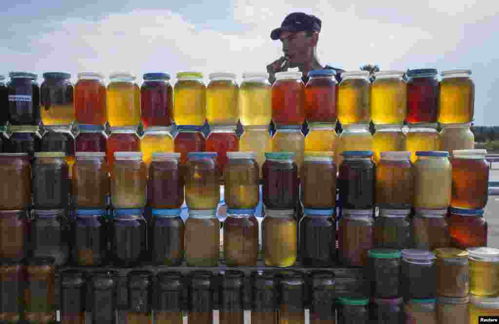 A vendor, who is also a beekeeper, sells honey at a roadside market north of Astana, Kazakhstan. (Reuters/Shamil Zhumatov)