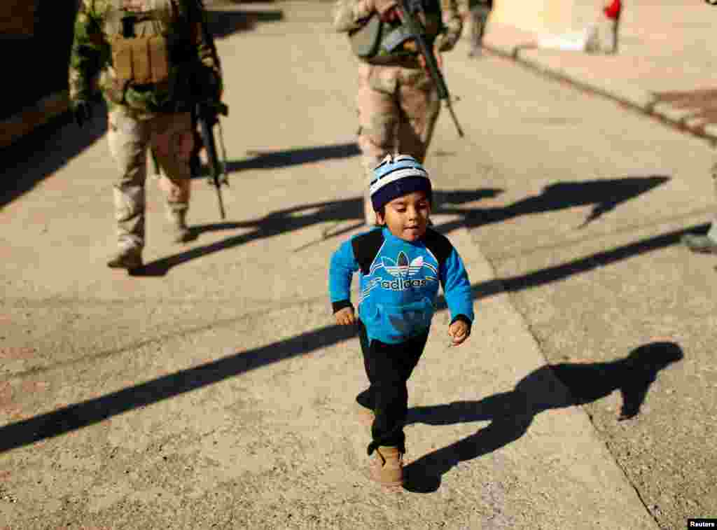 A child walks in front of Iraqi Army soldiers during an operation against Islamic State militants in the Intisar neighborhood of eastern Mosul. (Reuters/Ahmed Jadallah)