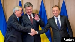 Ukrainian President Petro Poroshenko (center) shakes hands with European Commission President Jean-Claude Juncker (left) and European Council President Donald Tusk at the EU Council in Brussels on March 17.