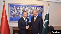 Pakistan's Foreign Minister Shah Mehmood Qureshi shakes hand with State Councillor and Foreign Minister Wang Yi at the Ministry of Foreign Affairs in Islamabad on September 8.