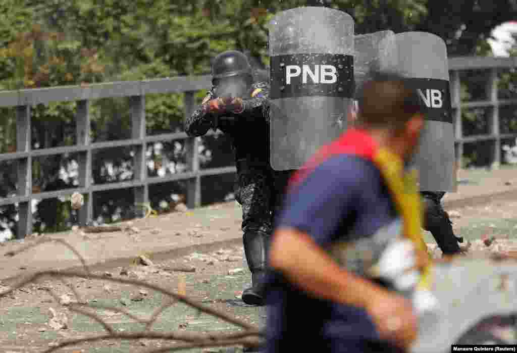 A police officer fires rubber bullets during a protest against Venezuelan President Nicolas Maduro's government in Caracas on January 23. (Reuters/Manaure Quintero)