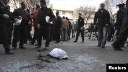 Policemen gather evidence at a bomb blast site in Tehran, which killed nuclear scientist Mostafa Ahmadi Roshan on January 11.