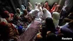 Mourners sit around the body of a boy who was killed in a bomb blast in Karachi in August.