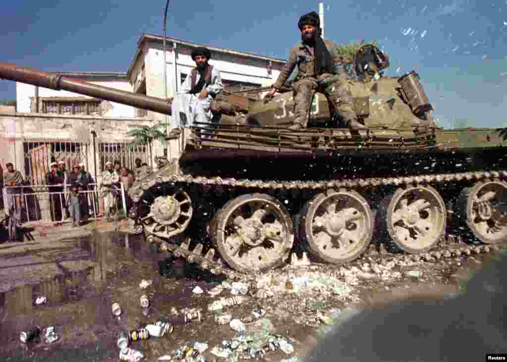 Taliban enforcers pop beer cans under a Soviet tank in Kabul. Alcohol was also strictly forbidden. Punishments for offenders against the Taliban's Shari'a edicts were often gruesome, and public.