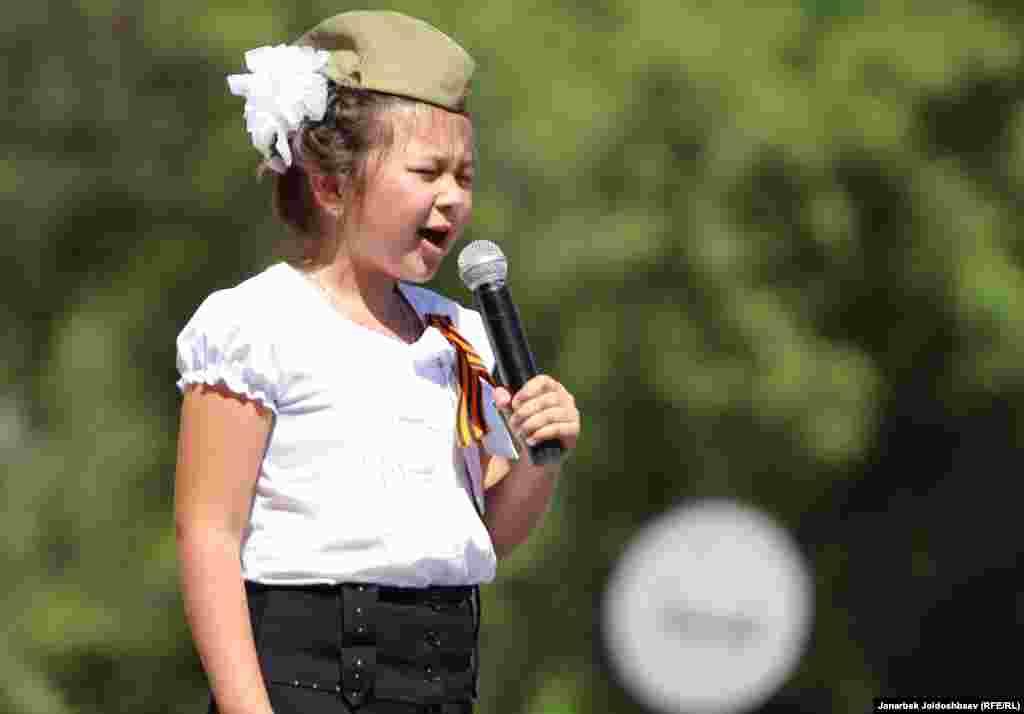 دختری در حال خواندن سرود در مراسم روز پیروزی در بیشکک، قرقیزستان