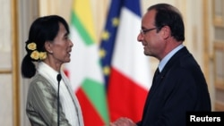 Myanmar pro-democracy leader Aung San Suu Kyi shakes hands with French President Francois Hollande as they attend their joint news conference at the Elysee Palace in Paris on June 26.