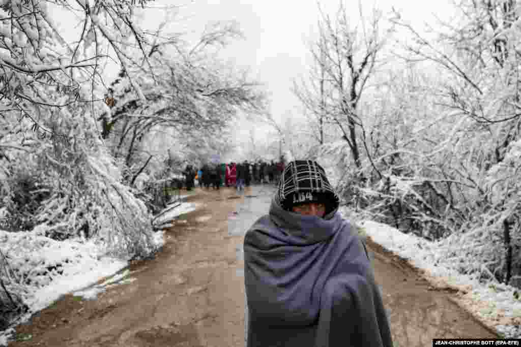 A migrant walks on a winter's day at the Vucjak refugee camp outside Bihac, northwestern Bosnia-Herzegovina. (epa-EFE/Jean Christophe Bott)​