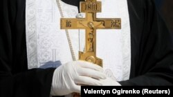 An Orthodox clergyman in Ukraine wears protective gloves, as a preventive measure against the coronavirus during a ceremony to bless Easter cakes earlier this week.