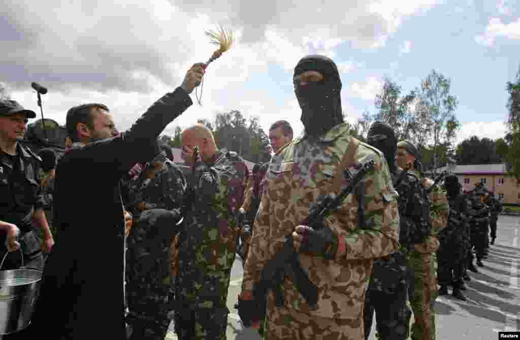 "A clergyman sprinkles holy water on members of the ""Donbass"" self-defence battalion attending a ceremony to swear an oath of allegiance for a reserve unit of the National Guard of Ukraine, near Kyiv, June 23. (Reuters/Valentyn Ogirenko)"