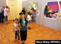 Мультфильм кейіпкерлері суреттерінің қасында тұрған балалар. Қарағанды, 6 тамыз 2014 жыл.