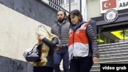 На фото: Турецкие полицейские ведут одну из женщин, задержанных в ходе рейда.