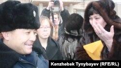 Полиция офицері оппозиция белсендісі Маржан Аспандияроваға (оң жақта) сотқа шақыру қағазын тапсырды. Алматы, 30 қаңтар 2012 жыл.