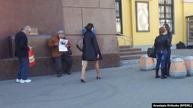 Один из спекулянтов предлагает билеты, сидя у театра