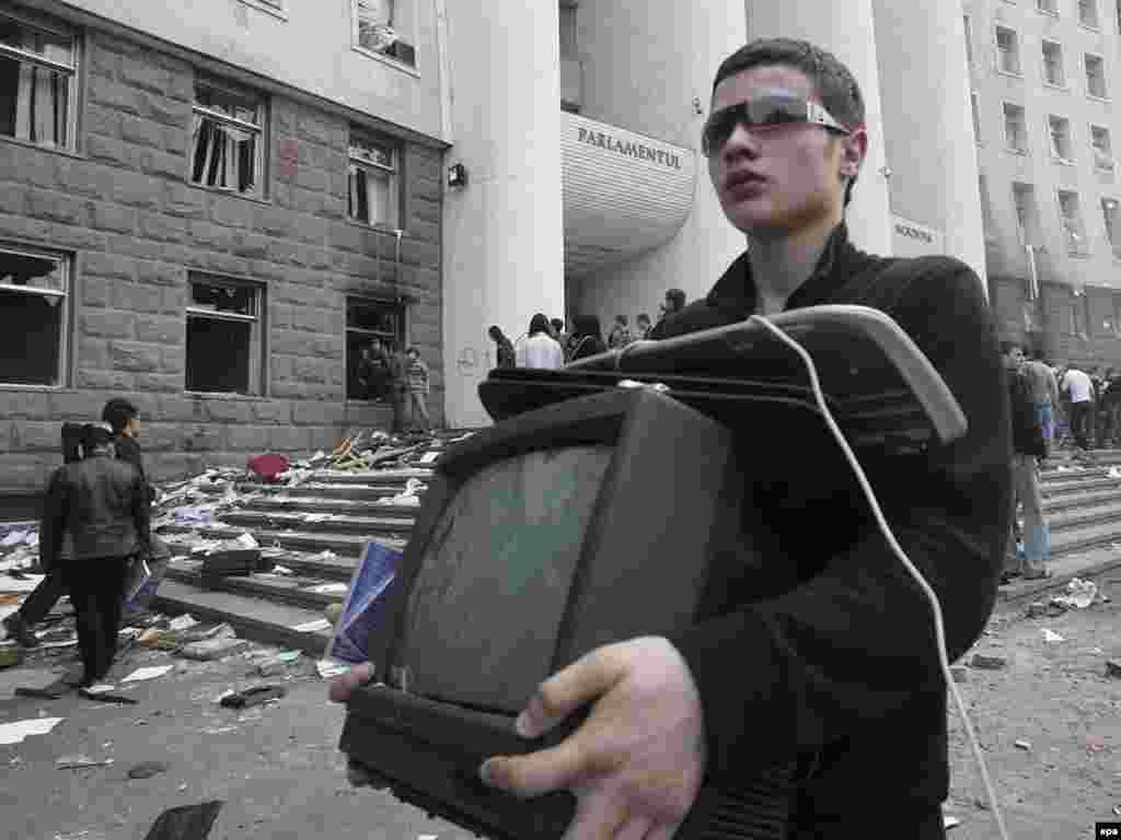 Молодой человек выносит телевизор из захваченного демонстрантами здания парламента Молдовы
