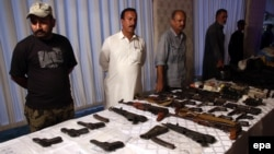 Pakistani security official displays weapons recovered during a security operation in Karachi on November 7.