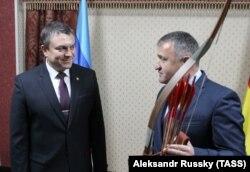 Анатолий Бибилов вручает Леониду Пасечнику осетинский лук со стрелами. Цхинвали, 17 декабря 2018 года