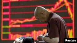 Хитой биржаси инқирозга юз тутган 7 июль куни сармоячи Пекиндаги брокерлик ширкати олдида акциялар нархини кўрсатувчи электрон таблодан маълумотлар олмоқда.