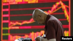 An investor takes notes in front of an electronic board showing stock information at a brokerage office in Beijing on July 7 as China's stock market crashed.