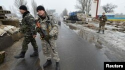 Ukrainian soldiers stand guard at a checkpoint on the outskirts of the town of Kostyantynivka in January.