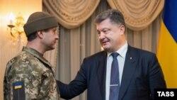 Ukrainanyň prezidenti Petro Poroşenko (s) boşadylan ukrain esgeri Andriý Hreçanow bilen, Kiýew, 1-nji dekabr, 2015