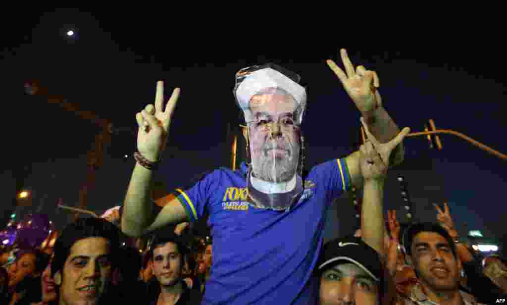 One of the celebrants at Vanak Square in Tehran wears a mask of the president-elect.