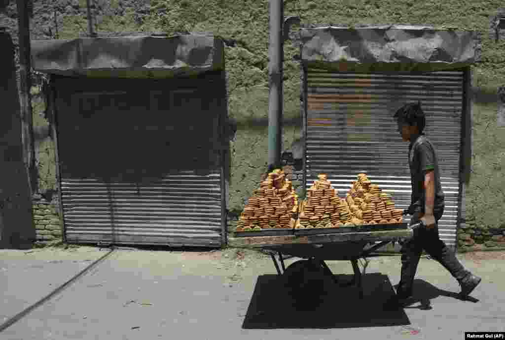 A young Afghan young boy carries traditional sweets with a handcart to a market ahead of the upcoming Eid al-Fitr holiday, marking the end of the holy fasting month of Ramadan in the old part of Kabul on June 13. (AP/Rahmat Gul)