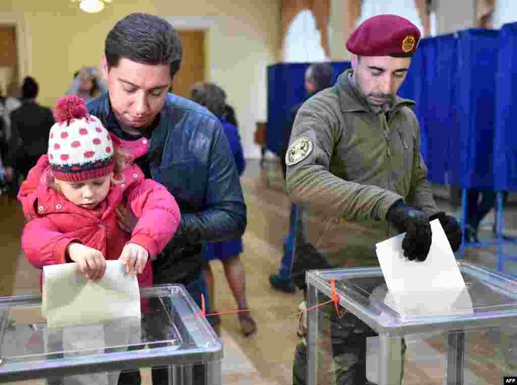 25 жовтня 2015 року. Люди голосують на одній з виборчих дільниць Києва під час місцевих виборів.Участь у місцевих виборах взяли майже 13,8 мільйона громадян, що склало 46,62% від загального числа виборців. Внутрішньо переміщені особи, а таких щонайменше 1,5 мільйона, права голосу були позбавлені