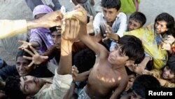 Pakistanis reach for food distributed from a truck in a village in Muzaffargarh district of Punjab Province.