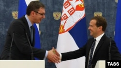 Serbian Prime Minister Aleksandar Vucic (left) and Russian Prime Minister Dmitry Medvedev shake hands at a press conference in Moscow on July 7.
