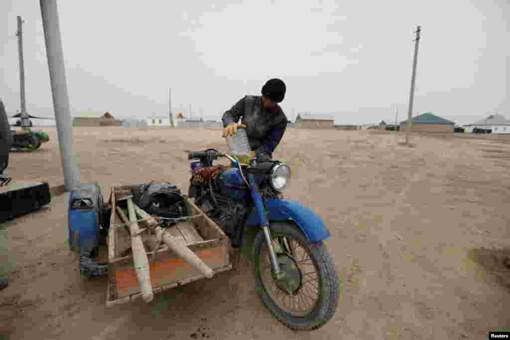 Ауылды жерде мотоцикл ыңғайлы көлік түрі саналады. Қаратерең ауылының тұрғыны мотоцикліне бензин құйып жатыр.