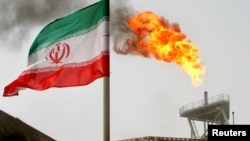 FILE PHOTO: A gas flare on an oil production platform in the Soroush oil fields is seen alongside an Iranian flag