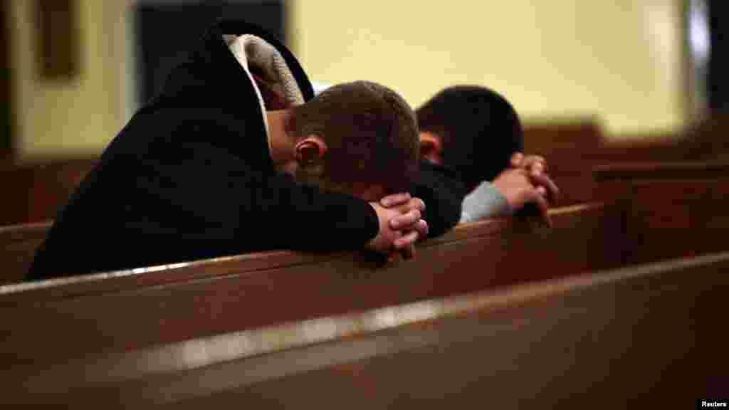 Родственники школьников молятся в церкве Святой Розы в Ньютауне