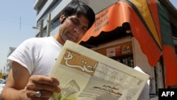 "A man reads a copy of the reformist ""Etemad"" newspaper in Tehran."