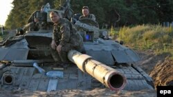 Ukrainian soldiers sit atop a tank that's dug in at a position outside Luhansk on June 29.
