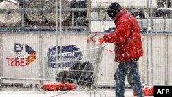 """Мъж с количка с покупки минава през площад в Скопие на фона на надпис """"ЕС за теб""""."""