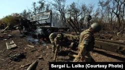 Ukrainian soldiers sort through the wreckage of an artillery convoy destroyed earlier by Russian firepower in September 2014.