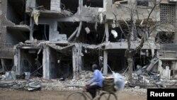 Уруштарда ураган үйлөрдүн жанынан өтүп бараткан велосипедчен киши. Сириянын борбору Дамасктын жанындагы Жобар аймагы. 27-октябрь, 2015-жыл